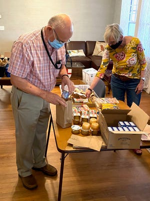 Emmanuel Episcopal Church attendees John Williams and Jeanni Pruitt packing lunches for the church's free meal program.