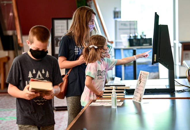 Aline Marchant, middle, 8, of Anderson self-checks out her children's books with her mother Marie Marchant, near her brother Mack, left, 10, at the Anderson County Main Library in Anderson Wednesday, June 24, 2020.