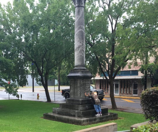 A woman lays her hands on the Confederate monument in front of the Rapides Parish Courthouse on Tuesday evening and prays. She was upset over the possible removal of the monument, which has stood outside the courthouse since 1962. It was erected in 1914 outside a former Alexandria City Hall.