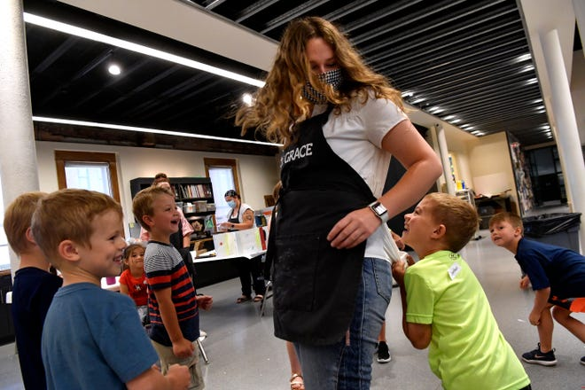 Jordan Worley, 7, laughs as he takes hold momentarily on Natalie Porter's shirt during a game of Statue at Wednesday's Sculpt It Camp at the Grace Museum. In the game, children had to freeze in place like a statue every time Porter turned around.