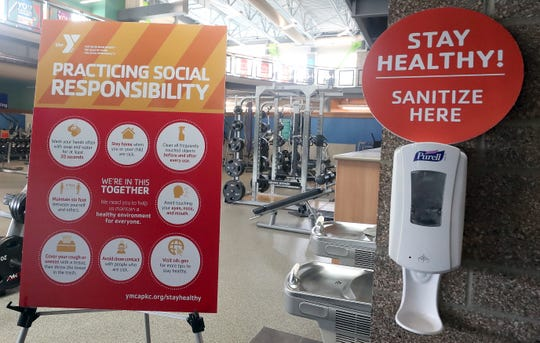 A hand sanitizer station and sign about social responsibility at the Haselwood Family YMCA in Silverdale on Wednesday.
