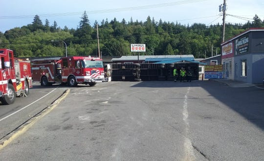Firefighters gather near a semi truck that overturned Tuesday in the Highway 3 curve in Gorst.
