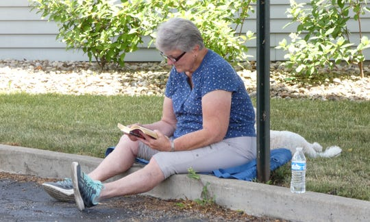 Ellie Wilhite reads a novel while she listens to music performed by Harvey & Friends outside the Crawford County Council on Aging building Wednesday.