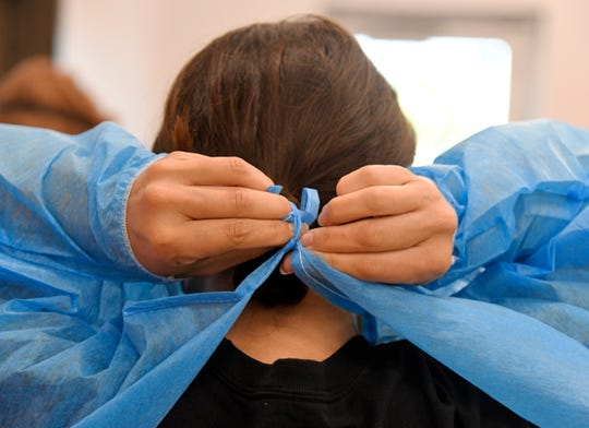 A medical worker puts on personal protective equipment before conducting testing.