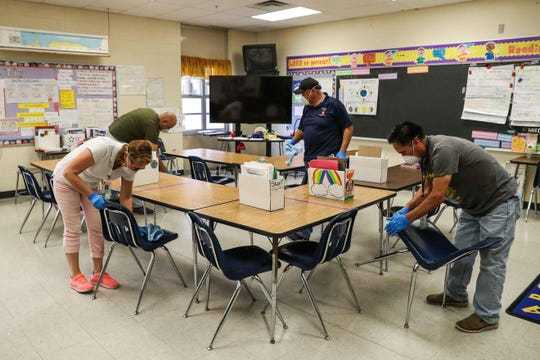 Employees clean a classroom in Austin. Draft guidelines from the state on how schools can reopen imposed few obligations on districts.