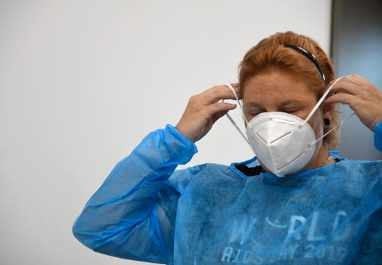 Medical assistant Katie Stewart puts on a N95 mask before COVID-19 testing, Wednesday, June 24, 2020, at the Coastal Bend Wellness Foundation. The clinic has remained opened during the pandemic and started coronavirus testing in late April.