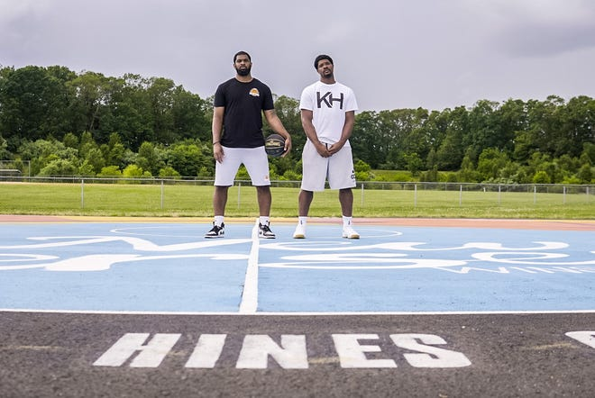 Brothers and former Timber Creek basketball standouts Tyler, left, and Kyle Hines stand on Team Hines Community Court, which was recently opened at Frank Donio Memorial Park.