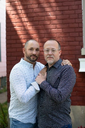 Chuck Beatty (right), with husband Chad Turner (left), pose outside their Covington home on Wednesday, June 24, 2020. Beatty and Turner got married in 2017.