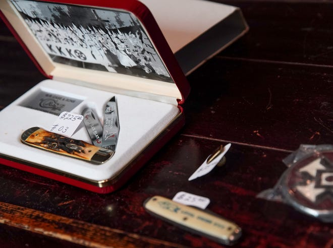 Ku Klux Klan items including two pocket knives and a cufflink sit on a back desk at Smith's Variety Thrift Store and Vendor Mall in Clarksville, Tenn., on Tuesday, June 23, 2020.