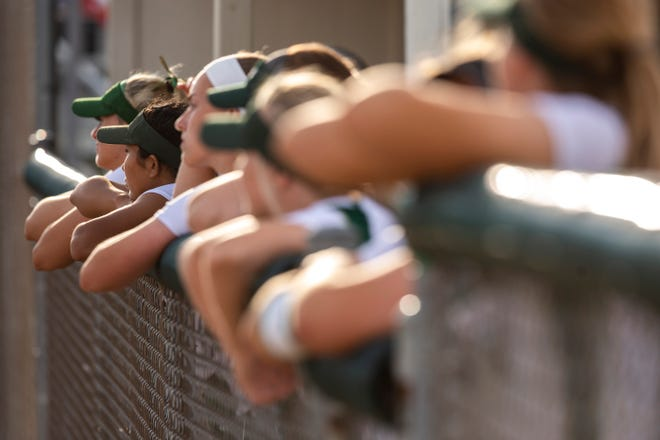 Iowa City West players lean over the dugout wall during a Class 5A softball game, Tuesday, June 23, 2020, at West High School in Iowa City, Iowa.