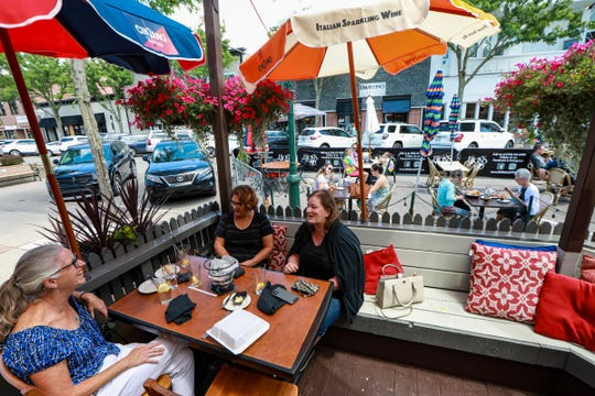 Childhood friends Carrie Majeske, 58, of Ann Arbor, Marisa Eppler, 57, of Plymouth, and Sue Dickson, 57, of Canton dine outside on the patio at E.G. Nicks restaurant in downtown Plymouth on Tuesday, June 23, 2020. The city of Plymouth closed off parking spaces and roads to accommodate more outdoor seating for restaurants.