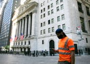 A man wearing a mask walks by the New York Stock Exchange, Tuesday, June 16, 2020.