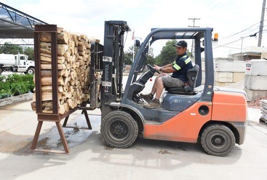 Matt Reed, 39, places firewood on a rack for customers to purchase at Eagle Supply in Southfield on Wednesday, June 24, 2020.