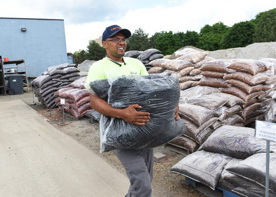 Cody Dawe carries bags of mulch to a customer's car at Eagle Landscaping & Supply Co. in Southfield. Manager  Deborah Eagle says she has troublerecruiting employees when many are collecting $600 per week from thefederal governmentin addition to their regular state unemployment benefit.