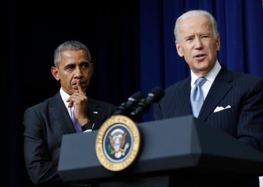FILE - In this Dec. 13, 2016, file photo, President Barack Obama listens as Vice President Joe Biden speaks in the South Court Auditorium in the Eisenhower Executive Office Building on the White House complex in Washington.