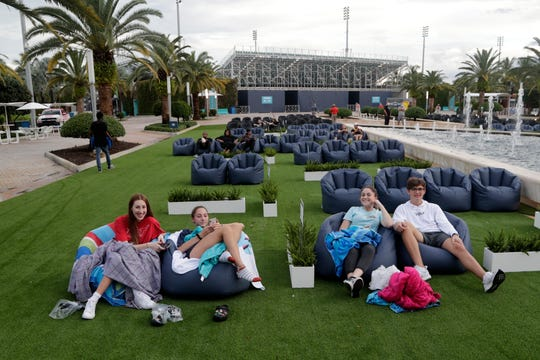People sit outdoors to watch a movie as part of a program offered by the Miami Dolphins at Hard Rock Stadium during the coronavirus pandemic in Miami Gardens, Fla.