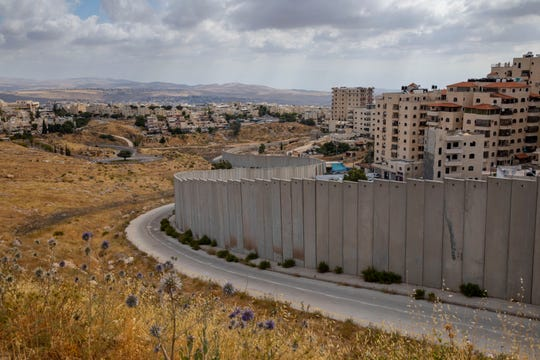 A view of Shuafat refugee camp is seen behind section of Israel's separation barrier in Jerusalem, Friday, June 19.