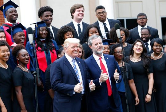 In this May 13, 2017 file photo, President Donald Trump poses with Liberty University president, Jerry Falwell Jr., center right, in front of a choir during of commencement ceremonies at the school in Lynchburg, Va.