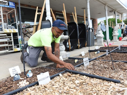 Cody Dawe, 28, Yard worker, arranges the mulch display  at Eagle Supply in Southfield, Mich., Wednesday, June 24, 2020. (Clarence Tabb, Jr./The Detroit News)