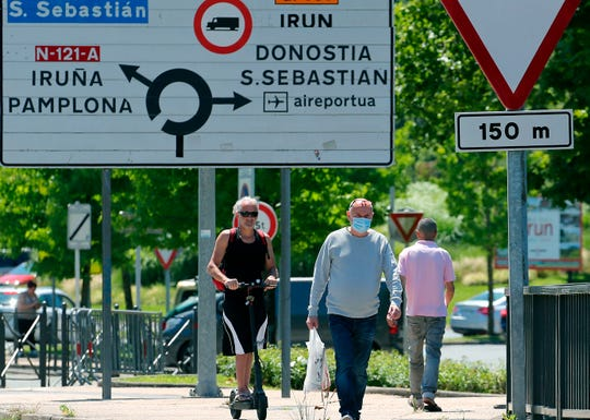 People cross the border between France and Spain at Behobie, southwestern France, Sunday, June 21, 2020.