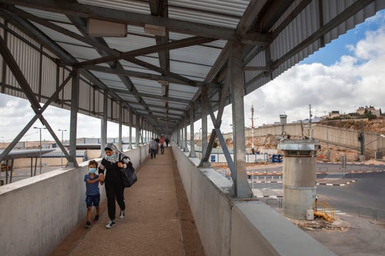 Palestinians cross a bridge at Qalandia checkpoint between the West Bank city of Ramallah and Jerusalem, Friday, June 19, 2020.