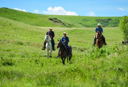 Troy Hennes, left, Harry Green, center, and Keagan Stroop, right, ride their horses as they prepare for a horseback trip through Montana's backcountry to raise money for cancer care and research.