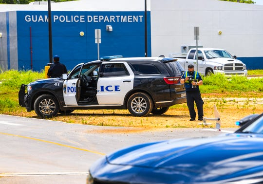 A Guam Police Department officer photographs the damage to a stop sign and a GPD official vehicle, seen in the background, during an investigation conducted after a hit-and-run collision that occurred near the entrance of its central precinct in Afame, Sinajana on Wednesday, June 24, 2020. Two officers were injured in the crash, acoording to Sgt. Paul Tapao, GPD spokesman.