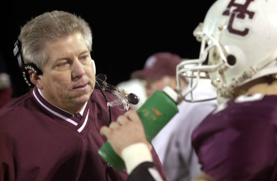 Henderson County coach Tom Duffy talks with quarterback Wes Peckenpaugh on the sidelines during the 2002 regional championship game at Colonel Stadium.
