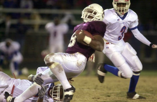 Henderson County's Alex Fendrick spins as he is brought down after a big gain during the 2002 regional championship game at Colonel Stadium.
