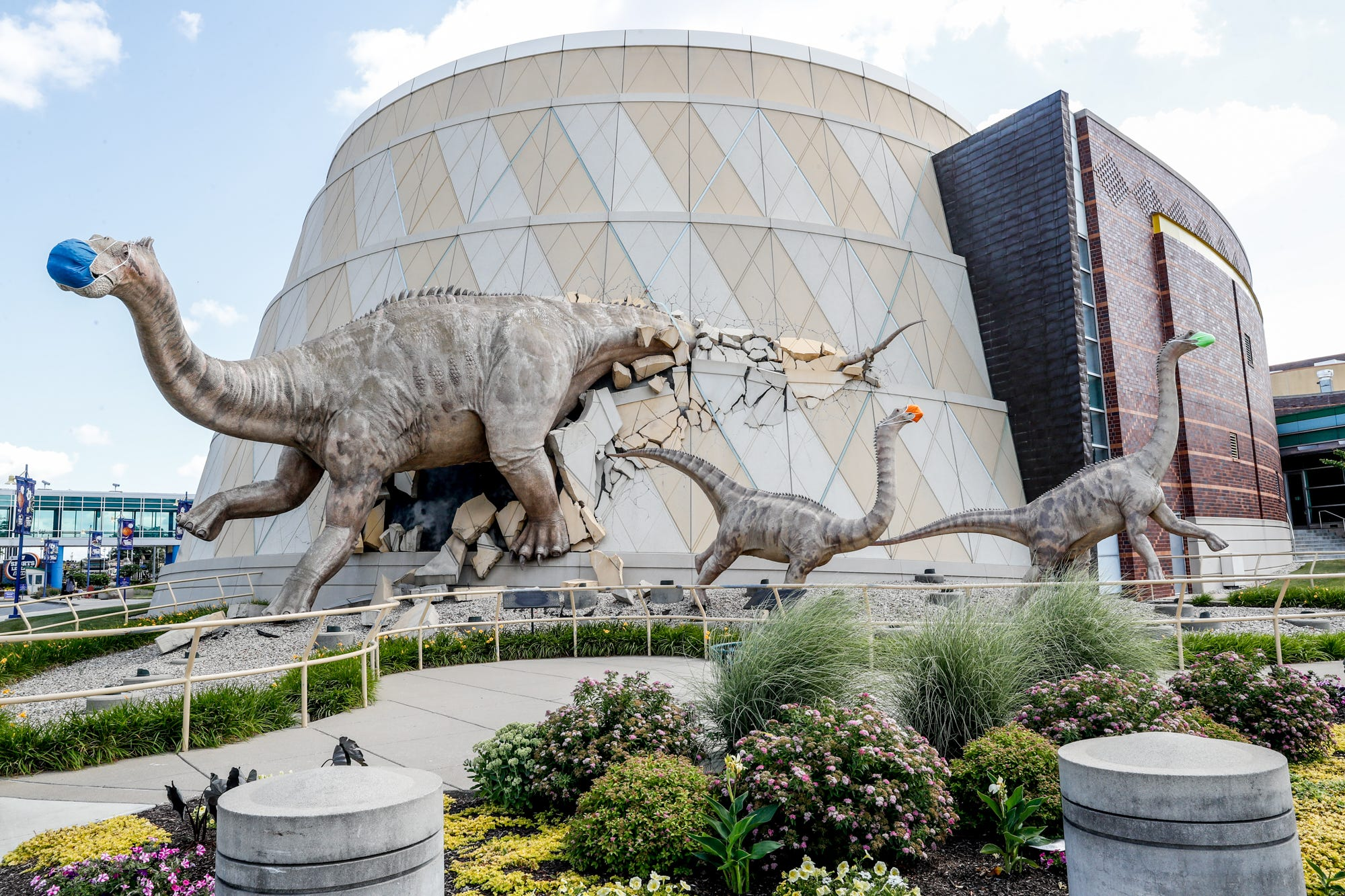Dinosaurs outside The Children's Museum of Indianapolis wear their own masks, Wednesday, June 24, 2020. The museum was working toward reopening to the general public.