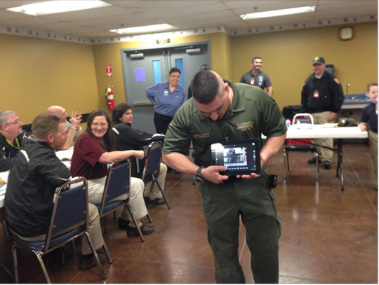 In this 2014 photo posted by the St. Landry Parish Sheriff's Department, Lt. Leon Boudreaux gives a demonstration to Wal-Mart employees of the SWAT equipment he and other team members use that was purchased with a WalMart Distribution Center grant.