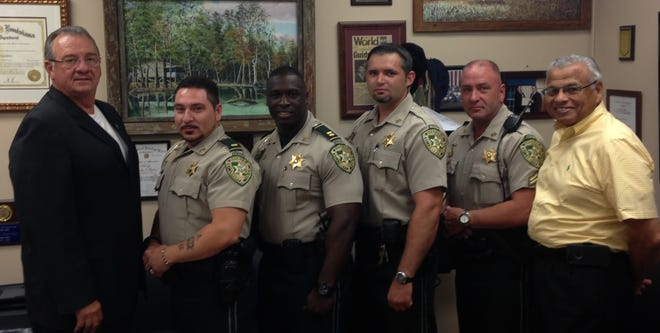 In this 2014 photo, St. Landry Parish Sheriff Bobby Guidroz, far left, stands next to Leon Boudreaux, a lieutenant in the sheriff's office at the time honored with the SWAT team. Also pictured are, to Boudreaux's right, Capt. Derrik Miles, Detective Josh Guillory and then-Cpl. Clay Higgins, now a congressman representing the area, as Chief Deputy Hilman Popillion looks on.