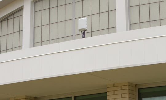 A wireless access point shown Wednesday, June 24, 2020, mounted on the front of Fowlerville High School, allows those parked outside the school to get Wi-Fi from that device.