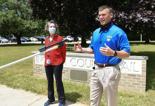 Ingham County Sheriff Scott Wriggelsworth speaks about steps being made to mitigate the spread of COVID-19 outside the Ingham County jail, Wednesday, June 24, 2020.  Eight people in custody have tested positive for COVID-19.  Also pictured is Ingham County Health Officer Linda Vail.