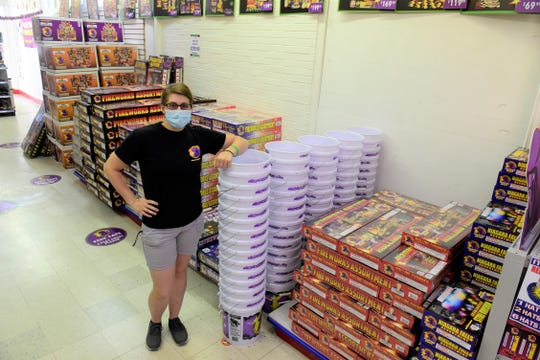 Abbey Mahon, assistant manager at Phantom Fireworks of Mansfield, stands with some of the bundles of fireworks ready for shoppers.