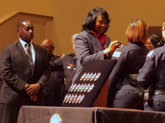 Gerald Darling, left, the district's chief of student services, and Carolyn Jackson, director of security, present badges to new school resource officers in October 2018.