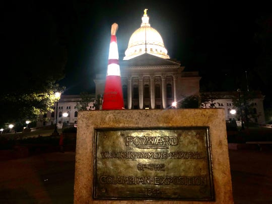 A cone sits atop the pedestal where the 'Forward' statue typically rests after protesters dragged the statue away June 24 in Madison.