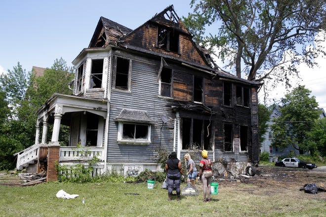 Workers clean up a duplex in the 2100 block of North 40th Street on Wednesday that was set on fire Tuesday as hundreds of people gathered where police earlier conducted an investigation into two missing teenage girls.