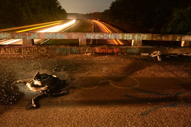 A burned tire remained on a Macon County overpass where a cross was discovered aflame June 4.