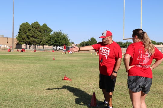 Loving Falcon coach Justin Parraz coaches a Loving Falcon athlete on June 23 during an early morning workout. Coaches are required to wear mask and social distancing is in effect at each workout.