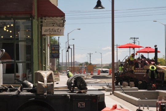 Crews work outside Artifacts Gallery, Wednesday, June 24, 2020, on a roundabout that is part of the ongoing Complete Streets project in downtown Farmington.