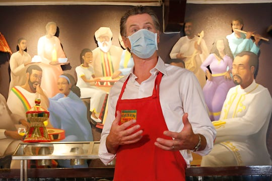 California Gov. Gavin Newsom, wears a face mask as he answers a reporters' question during his visit to the Queen Sheba Ethiopian Cuisine restaurant, in Sacramento, Calif., Friday, June 19, 2020. Newsom visited the restaurant that is participating in the Great Plates Delivered program that provides meals to older adults who are at-risk to COVID-19. (AP Photo/Rich Pedroncelli, Pool)