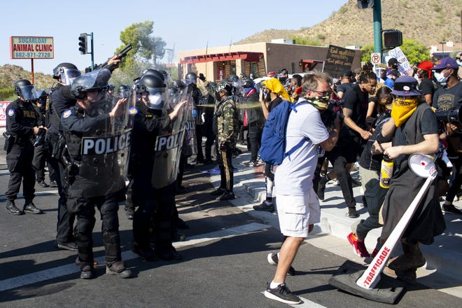 "Police dressed in riot gear fire ""less than lethal"" weapons at protesters and declare an unlawful assembly outside of Dream City Church in Phoenix, where President Donald Trump was holding a rally on June 23, 2020."