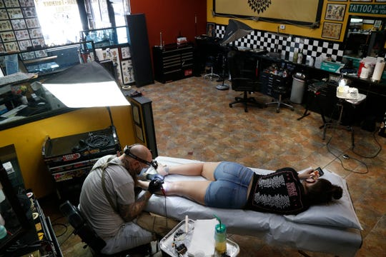Co-owner of Planet New York Tattoo Vincent Manco works on a new tattoo for Kelsie McDowell on June 23, 2020.