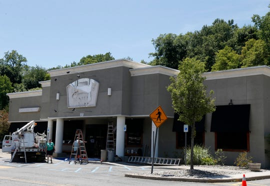 A crew removes signage from the location of the former Bonefish Grill in the Town of Poughkeepsie on June 24, 2020.