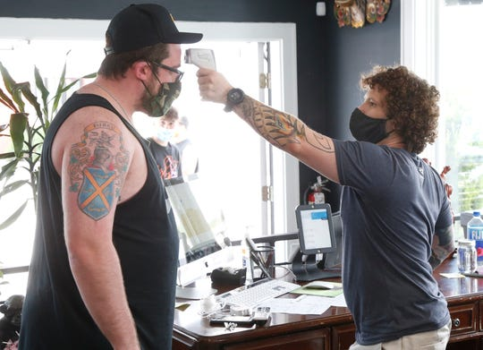 Office manager Nick Turner records the temperature of client Colin Furey of Saddle Brook New Jersey before he is allowed to get his tattoo worked on at Hudson Valley Tattoo Company in Wappingers Falls on June 23, 2020.