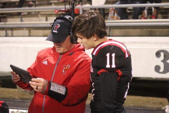 Parkway quarterback Eli Harper checks the gameplan with his coach.