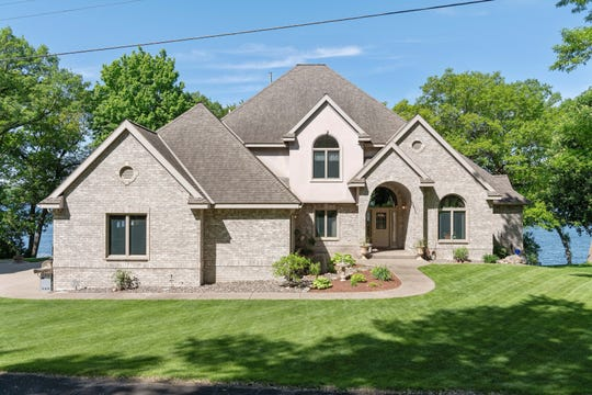 This two-story home welcomes family and friends with its winding sidewalk, brick exterior and arched entrance.