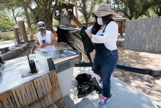 Sarah Borrego and Lily Gutierrez of the El Paso Zoo cover a bank of water fountains as they prepare to reopen after coronavirus closure. The zoo is taking measures to make the reopening safer for visitors.
