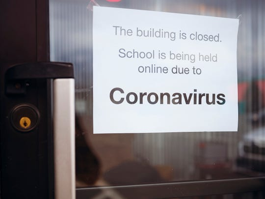 A door to a school with a sign stating that it is closed due to the Coronavirus COVID-19 pandemic.